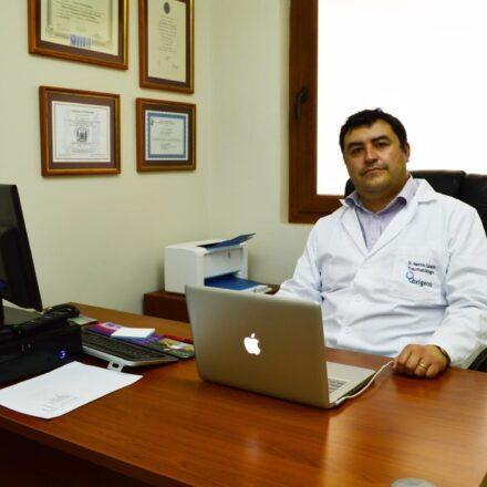 Dr Mauricio Cataldo en un box de Oxígeno sentado en escritorio mirando a la cámara